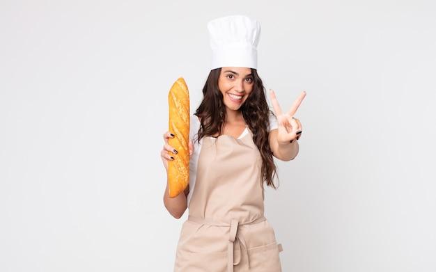 Mooie vrouw glimlacht en ziet er gelukkig uit, gebaart overwinning of vrede die een schort draagt en een stokbrood vasthoudt