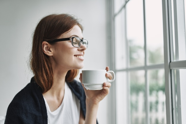 Mooie vrouw glimlacht en zit in de buurt van het raam met een kopje koffie in de hand