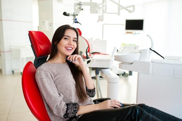 Mooie vrouw glimlacht in de tandartsstoel