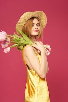 Mooie vrouw gouden jurk en boeket bloemen roze achtergrond