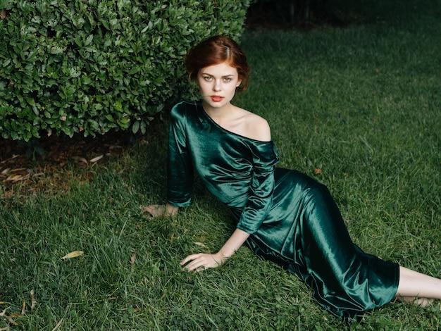 Mooie vrouw groene jurk gazon bush luxe frisse lucht