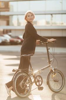 Mooie vrouw haar fiets buiten rijden