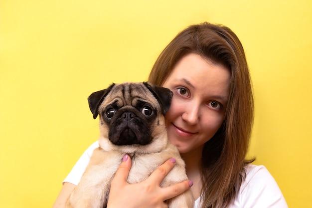 Mooie vrouw haar pug dog knuffelen