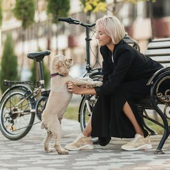 Mooie vrouw haar schattige hond aaien