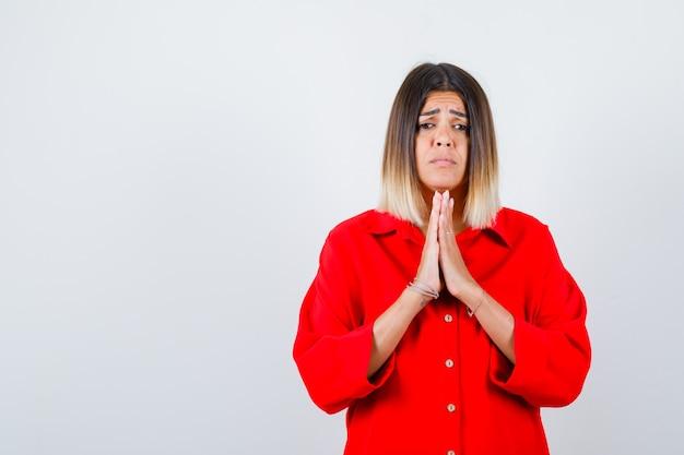 Mooie vrouw hand in hand in biddend gebaar in rode blouse en teleurgesteld, vooraanzicht.