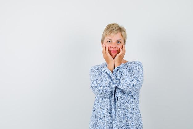 Mooie vrouw hand in hand op haar wangen in blouse met patroon en op zoek glamoureus. vooraanzicht. vrije ruimte voor uw tekst