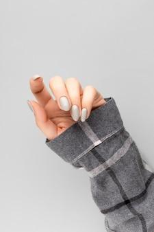 Mooie vrouw hand met manicure close-up op grijs.