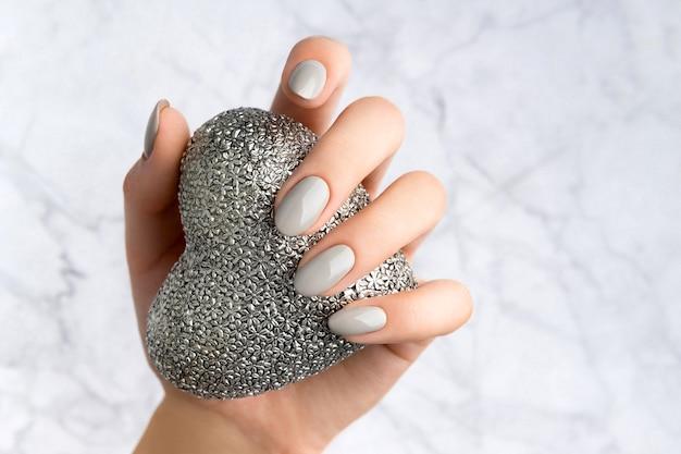 Mooie vrouw hand met manicure met zilveren hart.