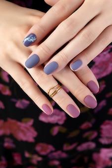 Mooie vrouw hand met paarse matte manicure op stof.