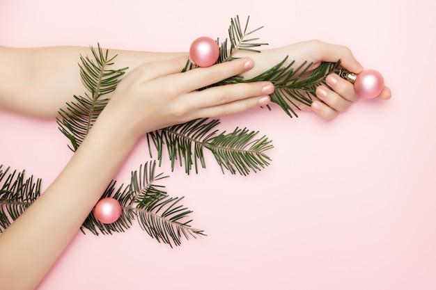 Mooie vrouw handen met een kerstboom tak met roze ballen op de roze achtergrond, met kopie ruimte. reclame concept van nagels of schoonheid. kerstuitverkoop.