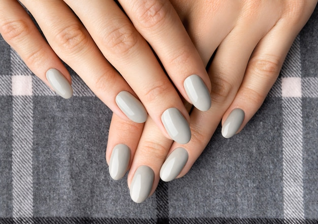 Mooie vrouw handen met manicure close-up op grijs.