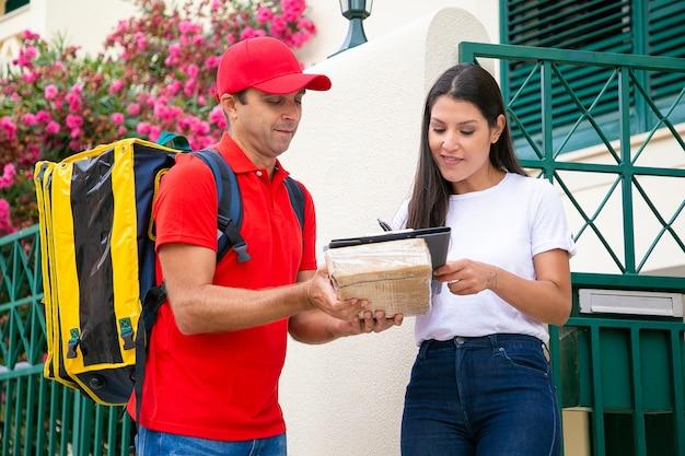 Mooie vrouw handtekening aanbrengend klembord en koeriersbedrijf doos. brunette vrouwelijke klant die levering van pakket van bezorger in rood uniform accepteert. thuisbezorgservice en postconcept