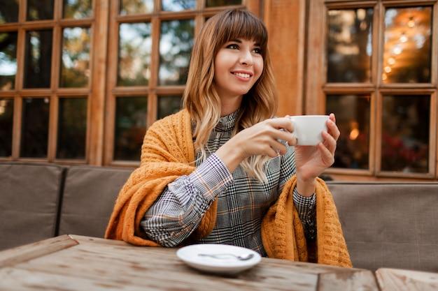 Mooie vrouw hebben een koffiepauze in gezellig café met houten interieur, praten via de mobiele telefoon. holding kopje warme cappuccino. winter seizoen. het dragen van een elegante jurk en een gele plaid.