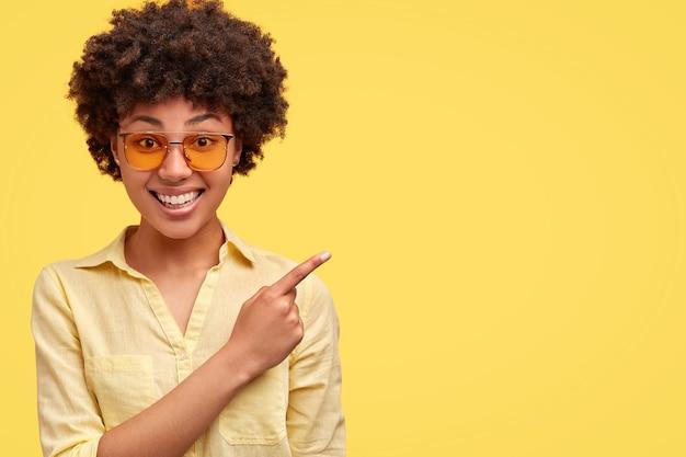 Mooie vrouw heeft een brede stralende glimlach, giechelt positief, heeft afro-kapsel, gekleed in een stijlvol shirt