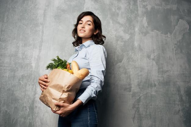 Mooie vrouw herfst shirts pakket met boodschappen gezonde voeding supermarkt donkere achtergrond