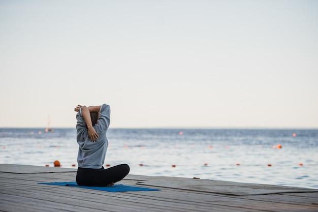 Mooie vrouw het beoefenen van yoga bij een meer