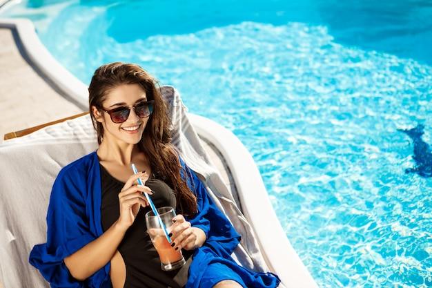 Mooie vrouw het drinken cocktail, die op chaise dichtbij zwembad ligt