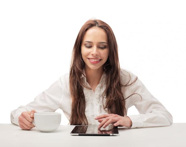 Mooie vrouw het drinken koffie en het gebruiken van een tablet