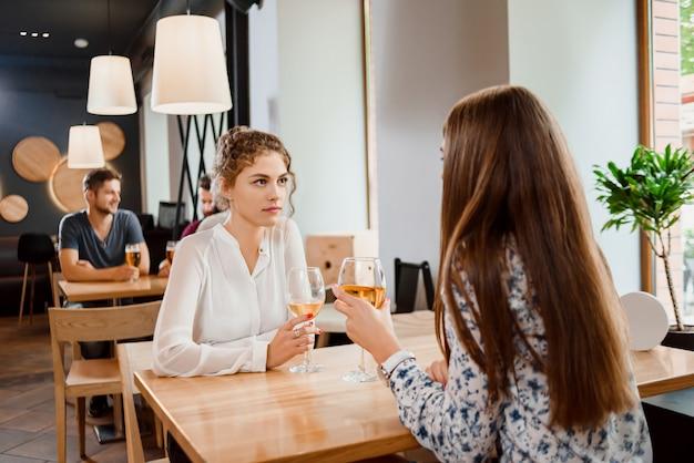 Mooie vrouw het drinken wijn met vrouwelijke vriend in restaurant.