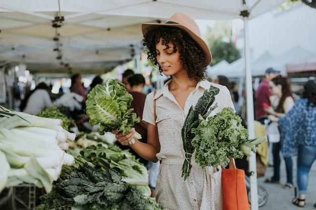 Mooie vrouw het kopen boerenkool bij een landbouwersmarkt