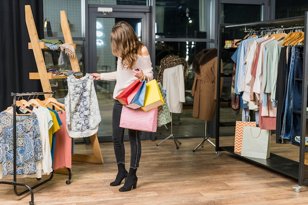 Mooie vrouw het kopen van kleren in winkel houden boodschappentassen in de hand