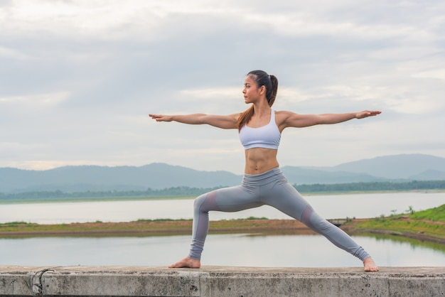 Mooie vrouw het praktizeren yoga door het meer met berg.