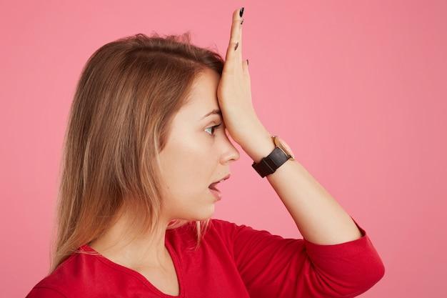 Mooie vrouw houdt de hand op het voorhoofd, herinnert zich iets belangrijks te doen, toont haar slechte geheugen