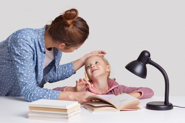 Mooie vrouw houdt dochters voorhoofd bij de hand, prijst en stimuleert haar om goed te studeren, poseert samen op het bureaublad. mooi meisje behaalde uitstekende cijfers op school, wordt geprezen door mama
