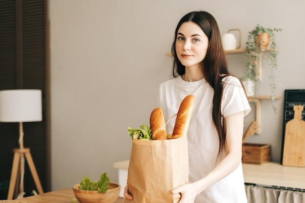 Mooie vrouw houdt eco boodschappentas met verse groenten en stokbrood