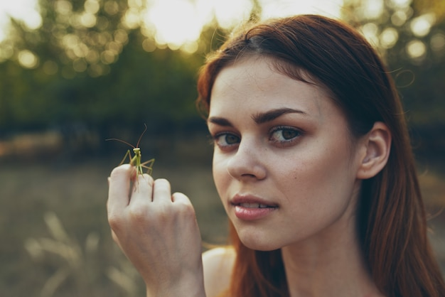 Mooie vrouw houdt een bidsprinkhaan op haar hand in de natuur op een weide in de zomer.