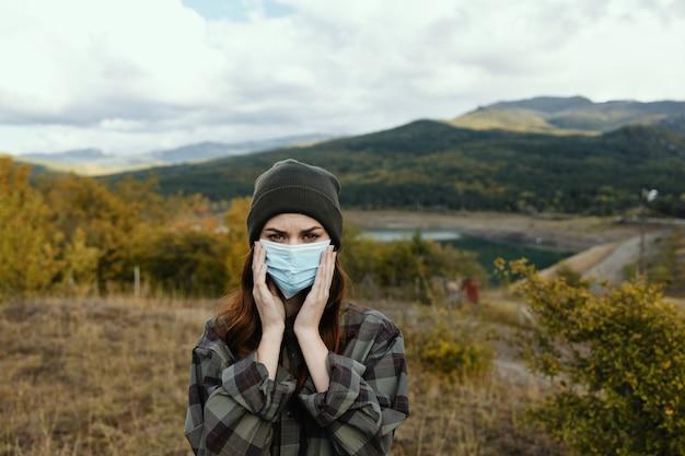 Mooie vrouw houdt een medisch masker op haar gezicht op de natuur in het bos.