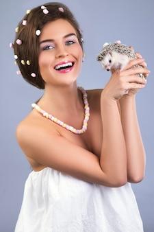 Mooie vrouw houdt een schattige kleine egel