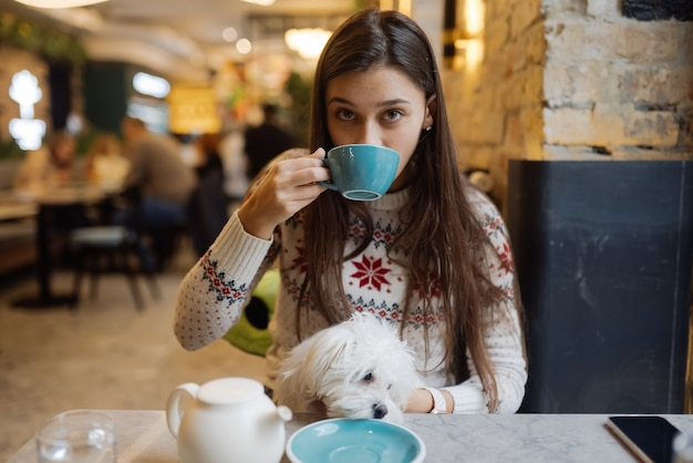 Mooie vrouw houdt haar schattige hond, drinkt koffie en lacht in café
