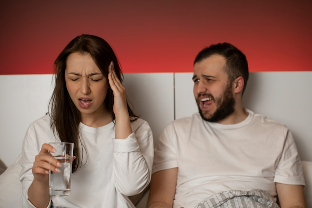 Mooie vrouw houdt hand bij tempel lijdt aan migraine, man schreeuwen tegen vrouw