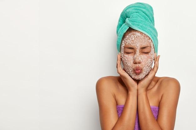 Mooie vrouw houdt lippen gevouwen en ogen gesloten, draagt een handdoek op het hoofd, maakt masker om het gezicht af te pellen na het douchen, heeft schoonheidsbehandelingen, modellen over witte muur, vrije ruimte