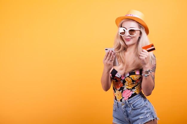 Mooie vrouw houdt smartphone en creditcard in studio op gele achtergrond