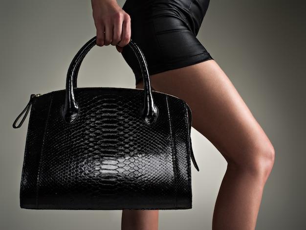 Mooie vrouw houdt stijlvolle zwarte tas. modieus meisje. glamour stijlvol concept. kunst. vrouw na het winkelen. onherkenbaar vrouwtje.