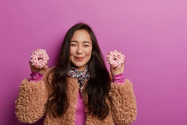 Mooie vrouw houdt twee smakelijke donuts in beide handen, heeft een blije uitdrukking, voelt verleiding als dieet blijft, draagt bruine jas