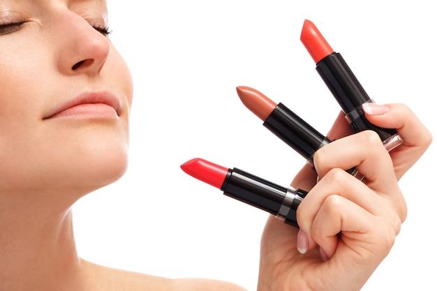 Mooie vrouw houdt verschillende lippenstiften