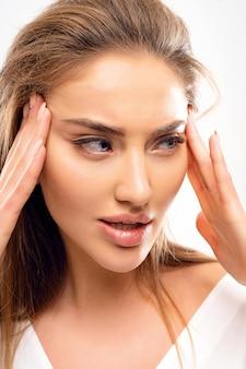 Mooie vrouw houdt zichzelf vast voor het gezicht en strekt zich uit om haar er jonger uit te laten zien grote lippen blauwe ogen wegkijken volume blond kapsel natuurlijke make-up