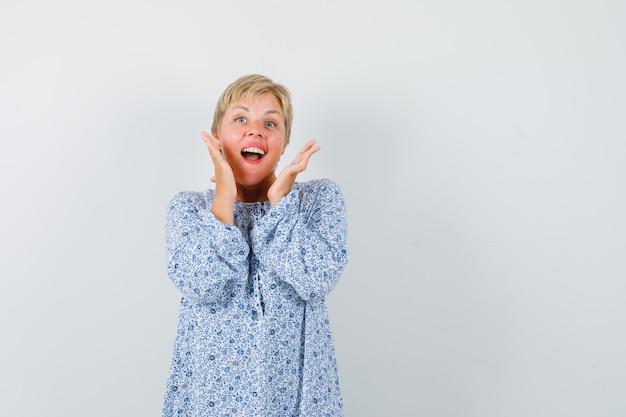 Mooie vrouw iemand bellen met luide stem in blouse met patroon en op zoek vrolijk. vooraanzicht. ruimte voor tekst