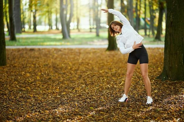 Mooie vrouw in activewear opwarmen in het park at