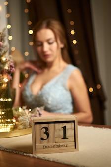 Mooie vrouw in avondjurk kalender in focus wazig achtergrond nieuwjaar