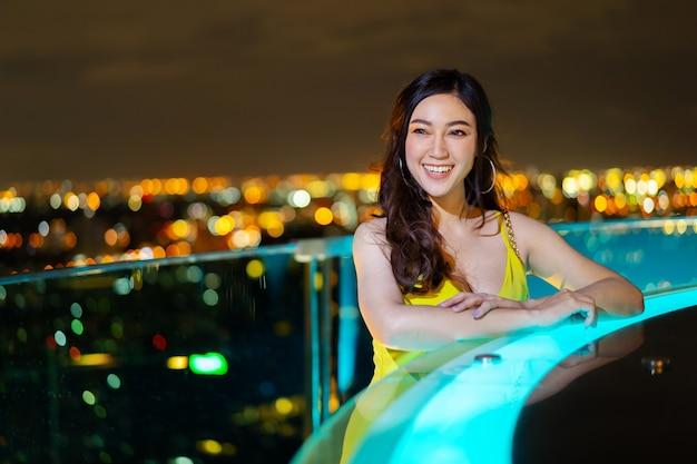 Mooie vrouw in avondjurk over nacht stad