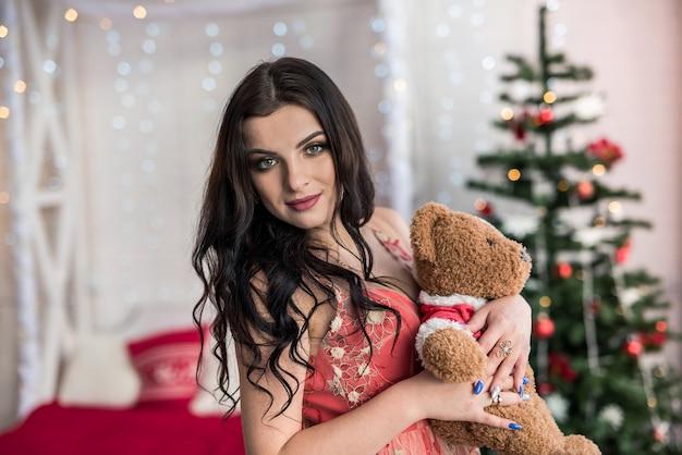 Mooie vrouw in avondjurk poseren met teddybeer