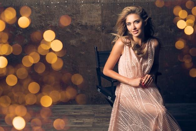 Mooie vrouw in avondjurk zittend in een stoel
