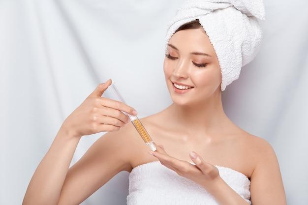 Mooie vrouw in badhanddoek op haar hoofd die schoonheidsinjectie houden en erop met glimlach kijken