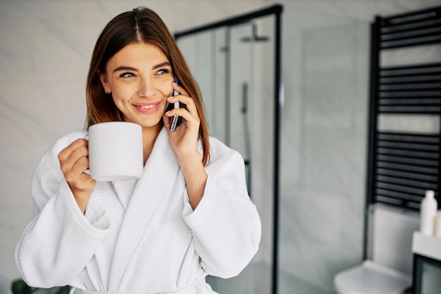Mooie vrouw in badjas praten aan de telefoon
