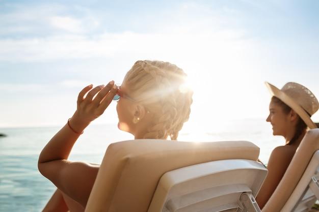 Mooie vrouw in badmode zonnebaden, liggend op ligstoelen in de buurt van de zee