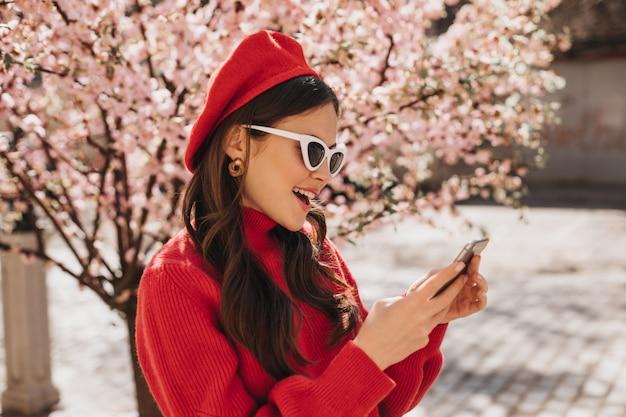 Mooie vrouw in baret en zonnebril chatten op telefoon in de buurt van sakura. buiten portret van dame in rode cashemere trui met mobiele telefoon